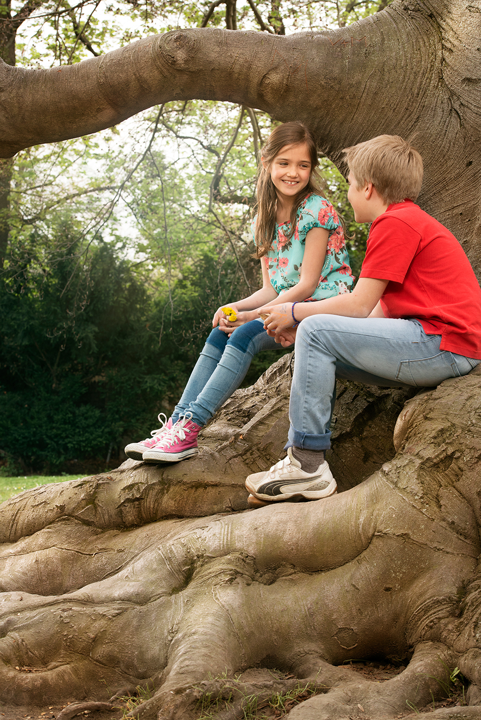 Two kids sitting on a tree