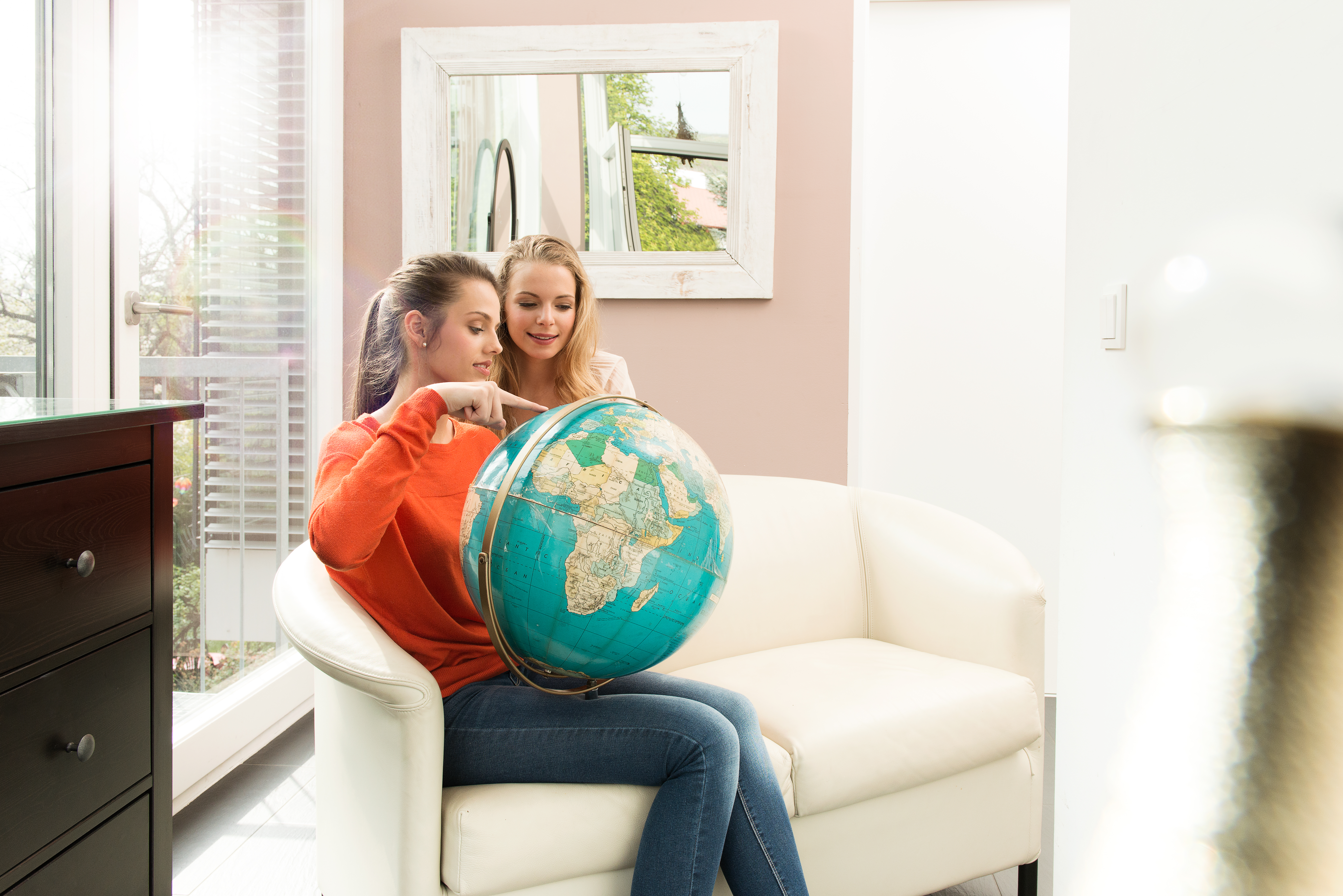 2 women, pointing at a globe